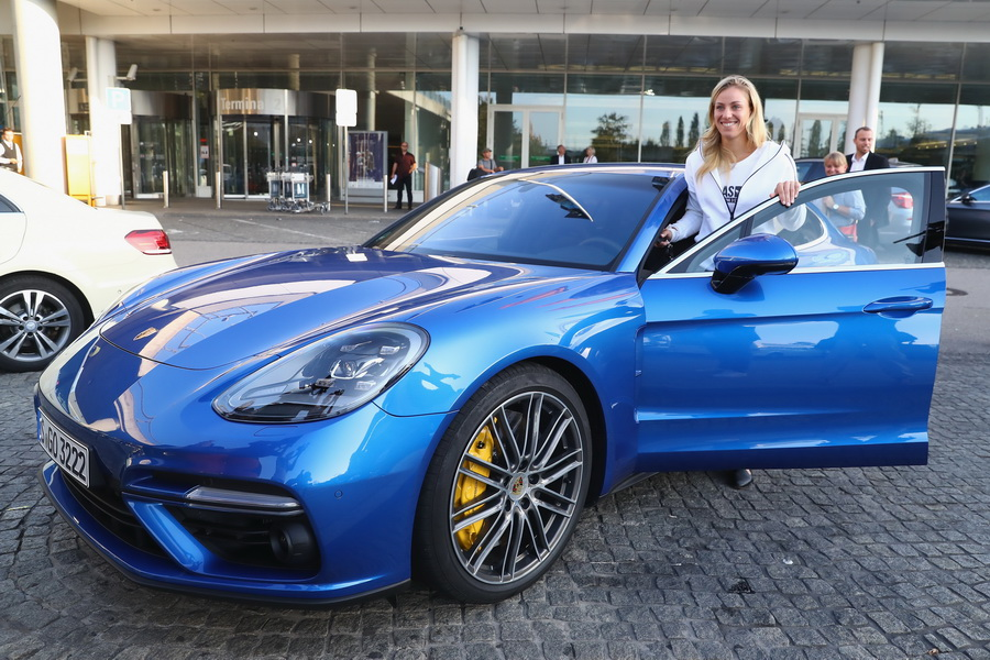 MUNICH, GERMANY - SEPTEMBER 13:  Angelique Kerber of Germany in front of the a new Porsche Panamera Turbo after returning as new Tennis World number One and winner of the US Open at Munich  Airport on September 13, 2016 in Munich, Germany.  (Photo by Alexander Hassenstein/Getty Images For Porsche)